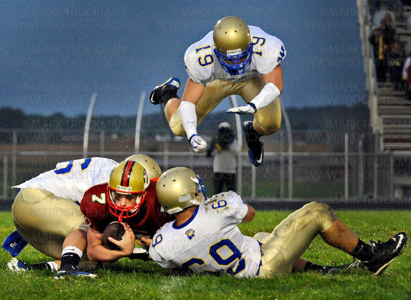 The first quarter sack of Cougars quarterback Mitchell Leidner (7) sends Wayzata senior Aaron Berg, top, into the air as his teammates, Michael Borillo, left, and Scott Siegel pull Leidner down to the grass Friday, Sept., 10, 2010, at Lakeville South HIgh School.  Wayzata beat the Cougars 45-20 in non-conference action.