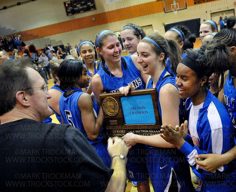 Hopkins girls basketball head coach Brian Cosgriff, left, is presented the section 6-4A championship trophy by his team after the Royals ended Wayzata's season with a commanding 71-44 defeat of the Trojans Wednesday, March 7, at Osseo High School.