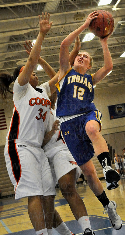 Trojans team captain, senior guard Kiana Nickel (12), barrels through the Cooper defense in first-half action during Wayzata's 57-54 defeat of the Hawks Wednesday, Dec. 12, in Plymouth.