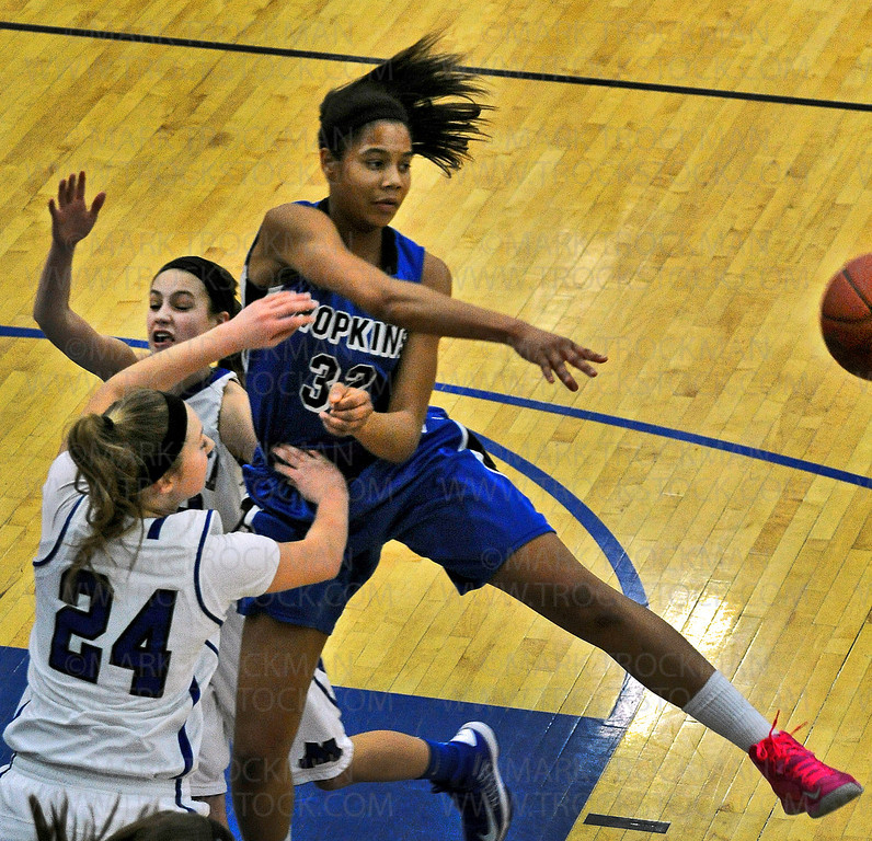 Hopkins senior guard Nia Coffey, right, makes an airborne pass to a teammate, skirting by Skippers freshman Courtney Fredrickson (24) during the Royals 78-55 Lake Conference win against Minnetonka Friday, Feb. 8, at Hopkins High School.