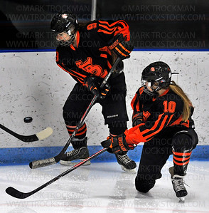 Orioles junior Brigid Duffy (9) and freshman Katie Fredrickson (10) eye the puck in action against Jefferson Saturday, Jan. 17, at Bloomington Ice Garden.