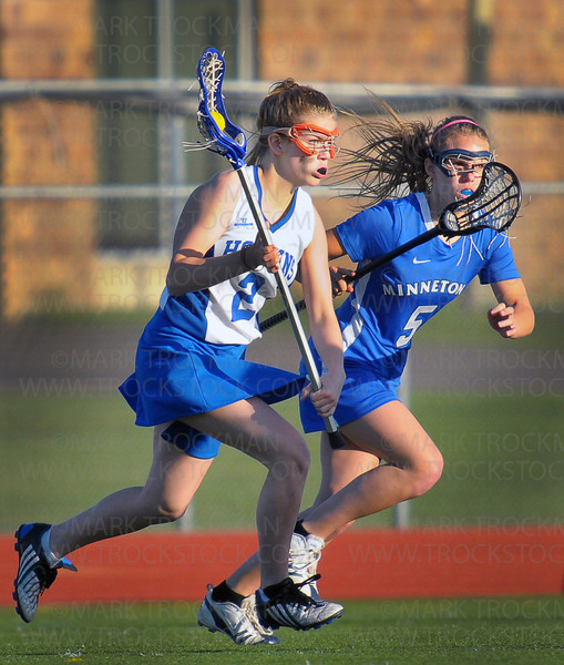 Hopkins sophomore Kristina Fredrickson, left, maintains possession as she sprints up field against Minnetonka junior Taylor DePauw Thursday, April 15, at Hopkins High School.  The Royals beat the Skippers 14-7 in conference action.