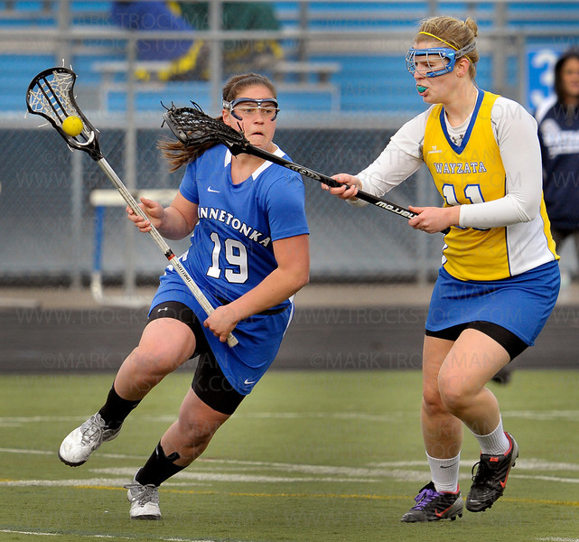 Minnetonka senior Hilary Duda (19) moves around Wayzata's Abby Nouis in the first half of the Skippers 13-6 win against Lake Conference rivals the Trojans Thursday, April 21, at Wayzata High School in Plymouth.