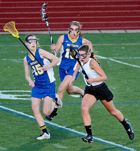 Royals junior Rachel Orbuch, right, is chased by Wayzata's Baylee Miller, left, and McKenna Lorenz, center, during the Trojans 9-6 defeat of the Royals Thursday, April 26, at Hopkins High School.