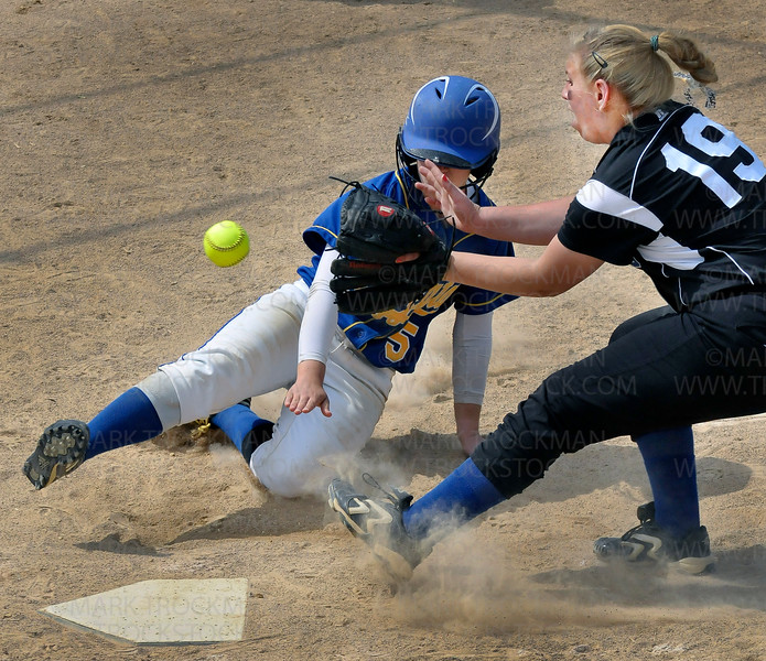 Hopkins junior pitcher Morgan Nybo, right, can't get the ball as Wayzata senior infielder Meg DuPuis slides and scores for the Trojans late in the game Thursday, June 2, at Richfield Middle School.  The Royals defeated Wayzata 9-2 to clinch the Section 6-3A Fastpitch Tournament title.