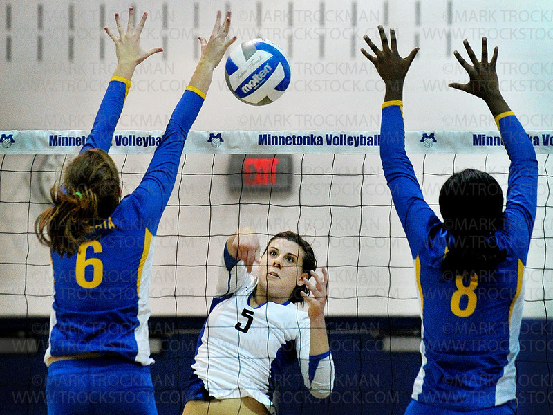 Minnetonka senior outside hitter Renee Hoffman, center, spikes the ball at Wayzata's Natalie Wilson (6) and Toni Okuyemi (8) Tuesday, Sept. 27, at Minnetonka High School.  The Trojans beat the Skippers in the five game match, 28-26, 25-21, 24-26, 19-25, 15-11.