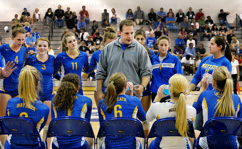 Wayzata varsity volleyball head coach Scott Jackson talks strategy with his team during a time out Tuesday, Sept. 27, at Minnetonka High School.  The Trojans beat their Lake Conference rivals, 28-26, 25-21, 24-26, 19-25, 15-11.