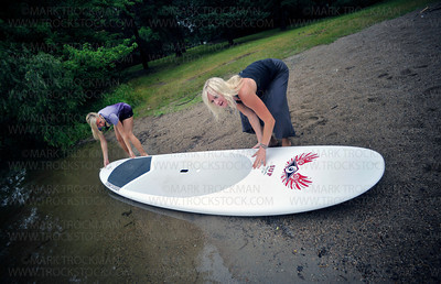 Wai Nani Surf & Paddle Co-Founders Holly Evans, left, and Stacia Fey lower an SUP board onto Summit Beach on Long Lake, Saturday, July 16, in Orono.