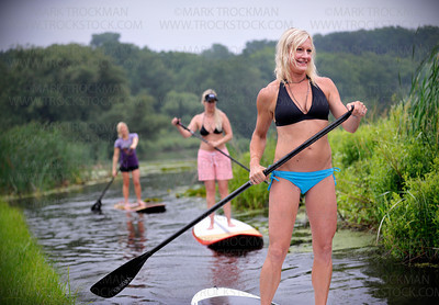 Wai Nani Surf & Paddle Co-Founders, from left, Holly Evans, Christine Thompson and Stacia Fey negotiate their SUP boards through a narrow channel on Long Lake Saturday, July 16, in Orono.