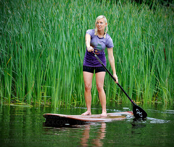Wai Nani Surf & Paddle Co-Founder Holly Evans paddles past a large patch of reeds on Long Lake in Orono Saturday, July 16.