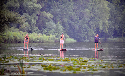 Wai Nani Surf & Paddle co-founders, from left, Stachia Fey, Christine Thompson and Holly Evans move across Long Lake on a muggy Saturday morning using their SUP paddles and boards, in Orono, July 16, 2011.