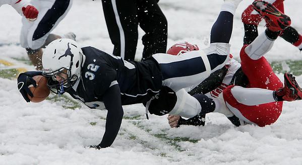 KEN YUSZKUS/Staff photo.  Peabody's Doug Santos dives forward trying to get some extra yardage at the Saugus at Peabody Thaksgiving football game.    11/27/14