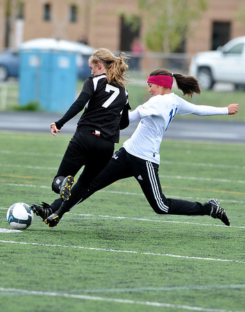 SOCCER<br /> Peak to Peak's Galen Roda kicks the ball away from Keile Kropf of Aspen.<br /> Photo by Marty Caivano/May 11, 2011