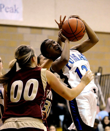 Peak to Peak's Khadijah Sayyid (right) is fouled by Faith Christian's Abigail Hegarty (back) and Myndee Thompson (left) during their baskeball game at Peak to Peak High School in Lafayette, Colorado February 4, 2010.  CAMERA/Mark Leffingwell