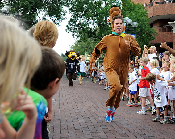 """Ryan Van Duzer, dressed as Scooby Doo, races to the finish line during the mascot race at the Pearl Street Mile on Thursday, Aug. 9, in Boulder. For a video of the race go to  <a href=""""http://www.dailycamera.com"""">http://www.dailycamera.com</a><br /> Jeremy Papasso/ Camera"""