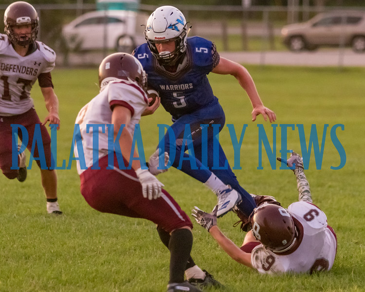 Peniel senior Andrew Dennin (5) evades a tackler and carries the ball downfield in the first half in the game against Old Plank. Fran Ruchalski/Palatka Daily News