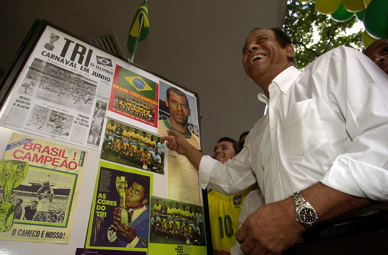 Brazilian soccer legend Carlos Antonio Torres points at a photo of himself at a exhibit in Rio de Janeiro, Brazil, Wednesday, May 28, 2000. Torres, captain of Brazil's 1970 World Cup champion 1970 national soccer team, aappeared to promote the exhibit in honor of the World Cup in Korea and Japan. The exhibit shows photos of the history of soccer in Brazil. Australfoto/Douglas Engle)