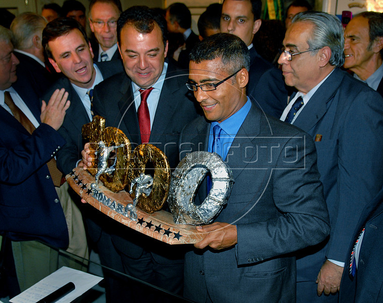 Brazilian soccer star Romario shows the trophy received from Rio de Janeiro's Governor Sergio Cabral, left, to mark his 1000 goals during a ceremony in Rio de Janeiro, Brazil, May 24, 2007. Romario, scored the 1,000th goal at his own count on 20 May, playing for Vasco da Gama in the Brazilian championship. (Austral Foto/Renzo Gostoli)