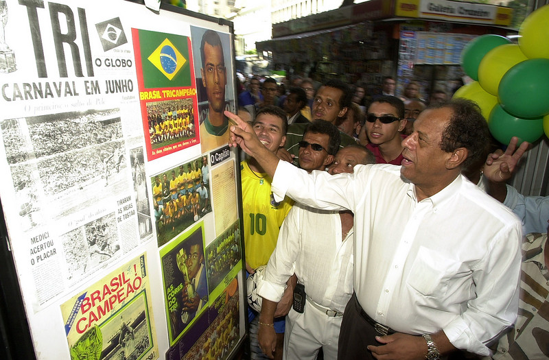 Brazilian soccer legend Carlos Antonio Torres points at a photo of himself at a exhibit in Rio de Janeiro, Brazil, Wednesday, May 28, 2000. Torres, captain of Brazil's 1970 World Cup champion 1970 national soccer team, aappeared to promote the exhibit in honor of the year's World Cup in Korea and Japan. The exhibit shows photos of the history of soccer in Brazil. Australfoto/Douglas Engle)