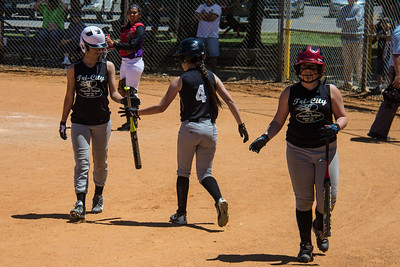 Addison and Mackenzie head back to the dugout after scoring in the first inning, while Erika heads to the plate