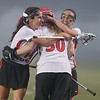 North Andover players Abbie Karalis, left, and Emily Sauls, right, celebrate with goalie Lauren Hiller after defeating Winchester.