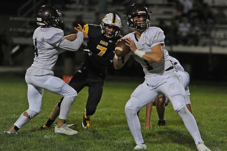 Berthoud quarterback Jake Lozinski looks for an open receiver as Thompson Valley's Jack Dyken (7) pursues while getting blocked by Austyn Binkly during a game Friday, Sept. 14, 2018 at Patterson Stadium in Loveland, Colorado. (Sean Star/Loveland Reporter-Herald)