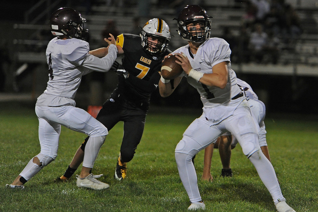 . Berthoud quarterback Jake Lozinski looks for an open receiver as Thompson Valley\'s Jack Dyken (7) pursues while getting blocked by Austyn Binkly during a game Friday, Sept. 14, 2018 at Patterson Stadium in Loveland, Colorado. (Sean Star/Loveland Reporter-Herald)