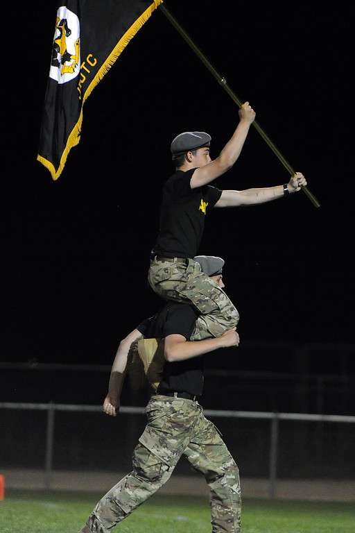 . A Thompson Valley JROTC member carries a flag while on the back of the shoulders of a classmate during a game Friday, Sept. 14, 2018 at Patterson Stadium in Loveland, Colorado. (Sean Star/Loveland Reporter-Herald)