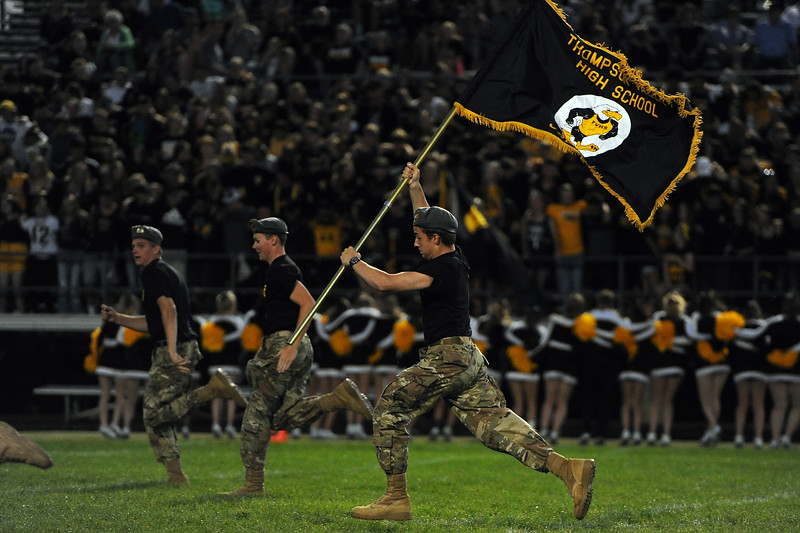 A member of the Thompson Valley ROTC carries a flag across the field between quarters during a game Friday, Sept. 14, 2018 at Patterson Stadium in Loveland, Colorado. (Sean Star/Loveland Reporter-Herald)