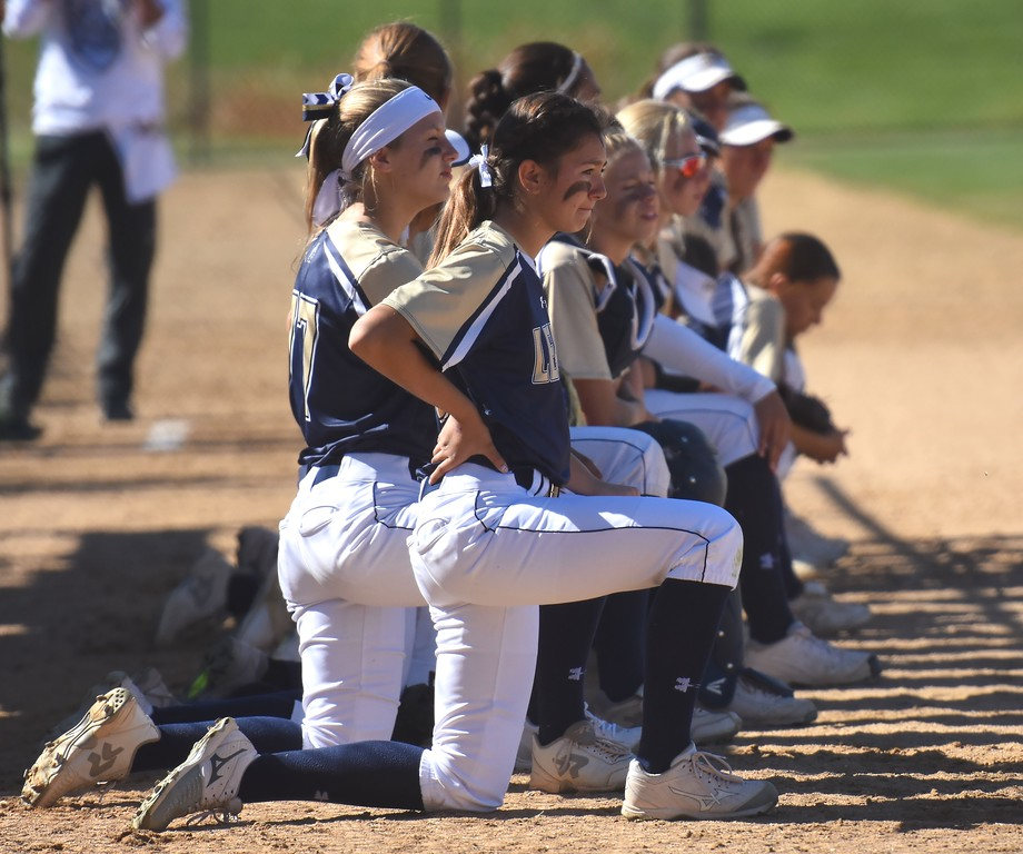 . The Legacy softball team takes a knee to watch their opponents during pregame infield drills at the softball state championships on Friday at Aurora Sports Park. (Photo by Brad Cochi/BoCoPreps.com)