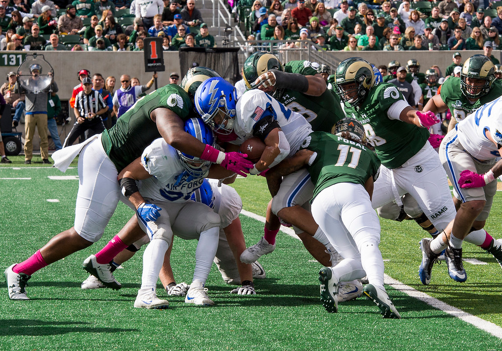 . Colorado State defenders including safety Jordan Fogal (11) tackle Air Force fullback Taven Birdow (23) during first-half action Saturday afternoon Oct., 28, 2017 at the CSU Stadium in Fort Collins. The Rams fell to the Falcons, 45-28. (Michael Brian/For the Reporter-Herald)