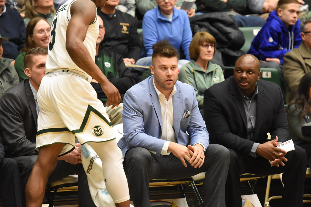 . Colorado State interim coach Jase Herl, middle, sits next to assistant Willie Glover, right, as Raquan Mitchell gets set to check in during their game February 22, 2018 at Moby Arena in Fort Collins. (Sean Star / Loveland Reporter-Herald)