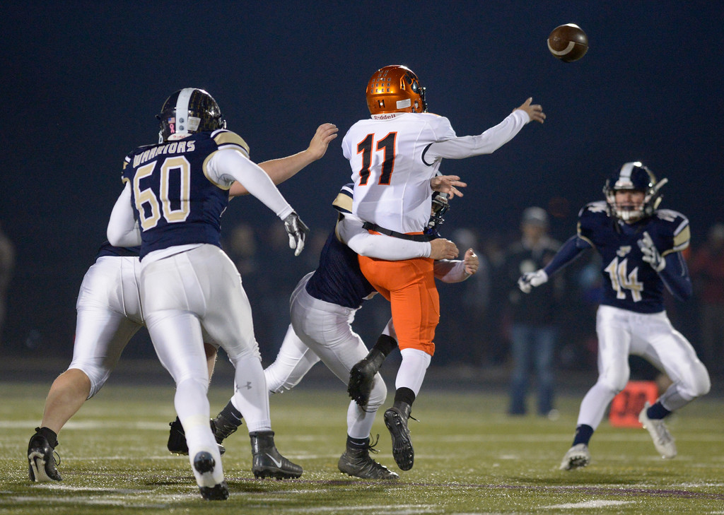 . Erie quarterback Dion Lucero gets the ball away as he is hit in the first quarter Friday night at Frederick High School. To view more photos visit bocopreps.com. Lewis Geyer/Staff Photographer Nov. 03, 2017