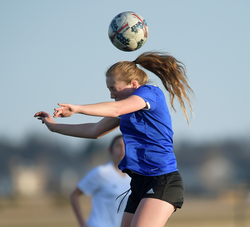 . Longmont\'s Kennedi Gesquiere heads the ball against Frederick in the first half Tuesday night at Frederick High School. To view more photos visit bocopreps.com. Lewis Geyer/Staff Photographer March 13, 2018