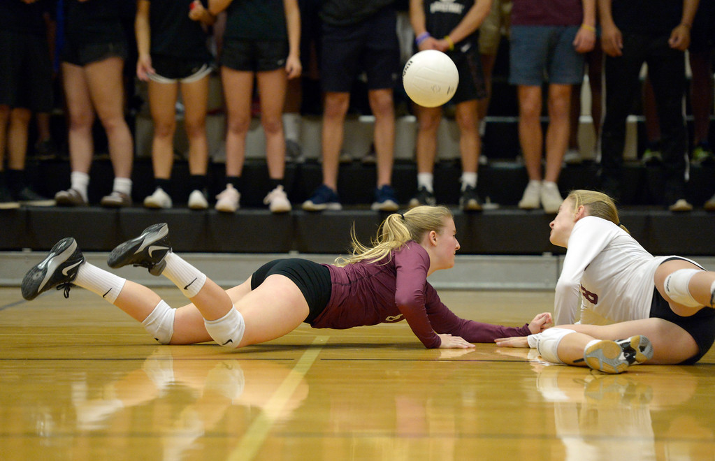 . Silver Creek\'s Tess Peter, left, and Katie James diver after the ball in the first game against Longmont at Silver Creek High School Thursday night. To view more photos visit bocopreps.com. Lewis Geyer/Staff Photographer Oct. 19, 62017