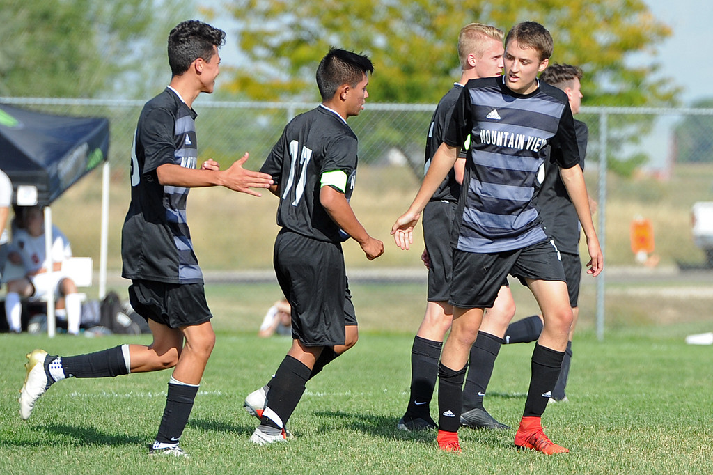 . Mountain View teammates congratulate Justin Condon after his goal during a game Tuesday, Sept. 4, 2018 at Mountain View High School in Loveland. (Sean Star/Loveland Reporter-Herald)