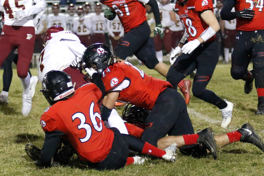 . Loveland�s Karl Dunlap (36) and Trey Cardenas (24) tackle Ponderosa�s Chris Shaw (7)  on Friday, Nov. 10, 2017, at Patterson Stadium in Loveland. (Photo by Lauren Cordova/Loveland Reporter-Herald)