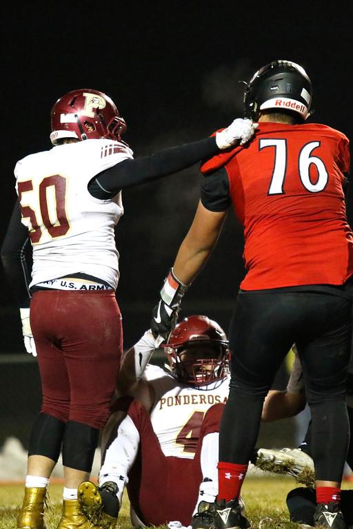 . Loveland�s Jayden Manu (76) helps Ponderosa�s Nick Hoff (4) up as Kyle Fehtinger (50) pats him on the back  on Friday, Nov. 10, 2017, at Patterson Stadium in Loveland. (Photo by Lauren Cordova/Loveland Reporter-Herald)