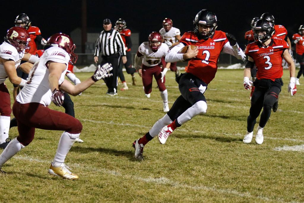 . Loveland�s Riley Kinney (2) runs the ball, avoiding Ponderosa�s Chris Shaw (7) with Zach Weinmaster (3) on defense on Friday, Nov. 10, 2017, at Patterson Stadium in Loveland. (Photo by Lauren Cordova/Loveland Reporter-Herald)