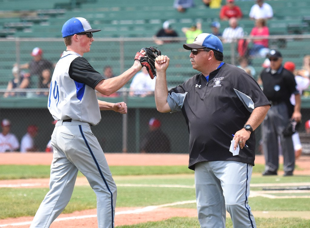 . Lyons head baseball coach Ken Rosales congratulates left fielder Justin Lear on making a good play to end the second inning during the Lions\' Class 2A state semifinal game against Rocky Ford on Saturday at Runyon Field Sports Complex in Pueblo.