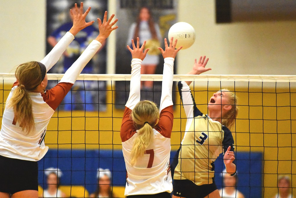 . Frederick freshman Kinley Lindhardt hits against a Mead double block during the teams\' match on Tuesday, Sept. 11, at Frederick High School.