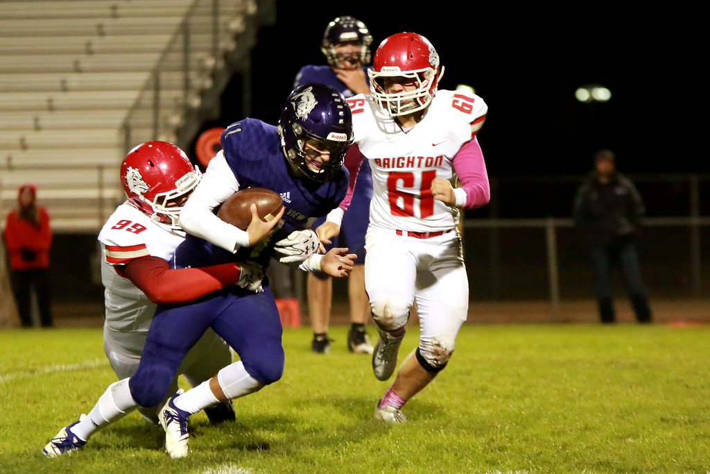 . Mountain View�s (11) Lukas Arthur defends the ball as Brighton�s (99) Casey Orange and (61) Codey Nelsen go for the tackle on Friday night�s game on Oct. 5, 2018 at Patterson Stadium in Loveland. Photo by Taelyn Livingston/ Loveland Reporter-Herald