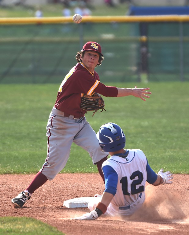 . Broomfield\'s Trenton Harris slides into second base while Rocky Mountain shortstop Tyler Mata-Lloyd turns a double play during the Eagles\' game against Rocky Mountain on Thursday, April 12, at Broomfield High School.