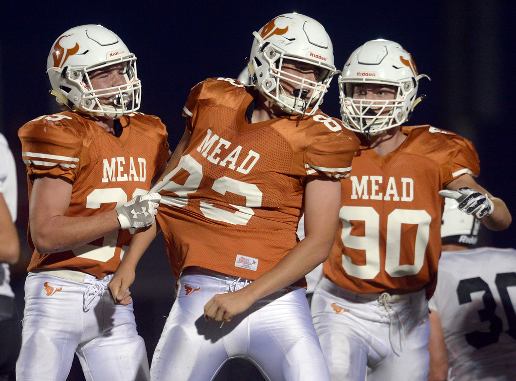 . MEAD, CO - SEPTEMBER 14, 2018: Mead\'s Tanner Leise is congratulated by teammates Kyle Johnson and Jay Olson after making a defensive stop against Roosevelt in the second quarter at Mead High School Sep. 14. (Photo by Lewis Geyer/Staff Photographer)