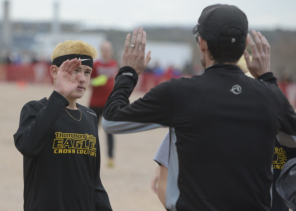 . Thompson Valley\'s Dylan Schubert high fives coach Matt Norton before the 4A boys state cross country championship on Saturday in Colorado Springs.