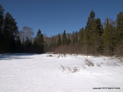 Looking back to stream we came from.  Ken broke through ice and tip of his snowshoe hooked under a burried branch.   It took several minutes of frustrating effort to extricate his foot from the trap.  Once on the lake, everything is peaceful.