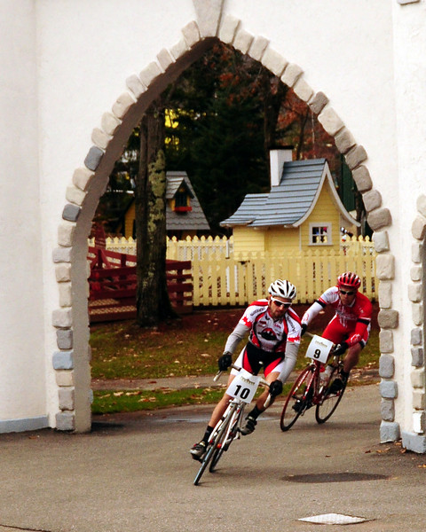 "The Porky Gulch Classic, a 3 stage bicycle race, presented by Great Glen Trails, of Gorham, NH, was held on November 6th & 7th, 2010. Pete Ostroski (#10), of Intervale, NH, and Scott Brooks, race into a castle, during the event's 2nd stage, ""The Story Land Criterium"", which was held at Story Land, a popular theme park in Glen, NH, on Saturday, November 6th, 2010."
