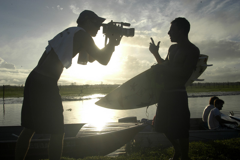 """Brazilian surfer Sergio Roberto, right, gives an interview before surfing on the tidal bore wave, known as pororoca, on the Araguari River, in Brazil's northern state of Amapa. The Araguari pororoca is possibly the most dangerous of all the Amazonian tidal bores, long feared by locals for wreaking havoc on their communities. wave crests at 2 to 3 meters and races at speeds between 30 to 50 kilometers per hour. To catch it, surfers must leap from a motorboat as the wave barrels upriver. Since the wave only occurs twice per day when the incoming ocean tide reverses the river flow for a time, there are not many chances to catch it, The name """"pororoca"""" comes from an Amazonian indigenous dialect meaning """"destroyer"""" or """"great blast."""" Since time immemorial, people have feared the roar which precedes the wall of water that capsizes boats and washes away anything in its path.(Douglas Engle/Australfoto)"""