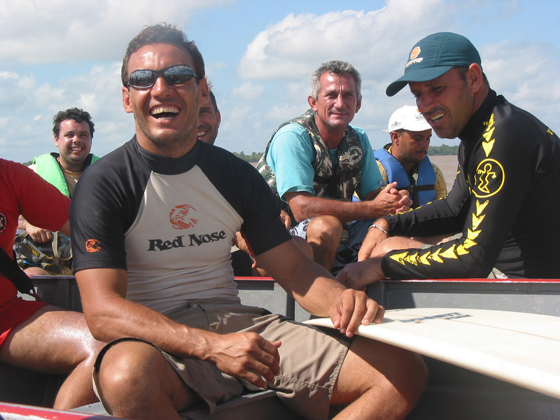 """Surfer Rodrigo Resende, left, shares a laugh with Picuruta Salazar, right during the """"I Pororoca Surf Challenge"""" on the tidal bore wave, known as pororoca, in the Araguari River of Brazil's Amazonian state of Amapa. Six reknown Brazilian surfers battled the wave in two elimination heats and one final to see who could surf the wave the longest. The Araguari pororoca is possibly the most feared of all the Amazonian tidal bores, and local residents of the remote areas surrounding the mouth of the river always feared the thunderous waves which capsizes boats and washes away anything in its path twice daily. Thanks to a group of daring surfers, they have begun to see the wave in a different way: as a tourist attraction to generate money in one of the poorest regions of Brazil.(AustralFoto/Douglas Engle)"""