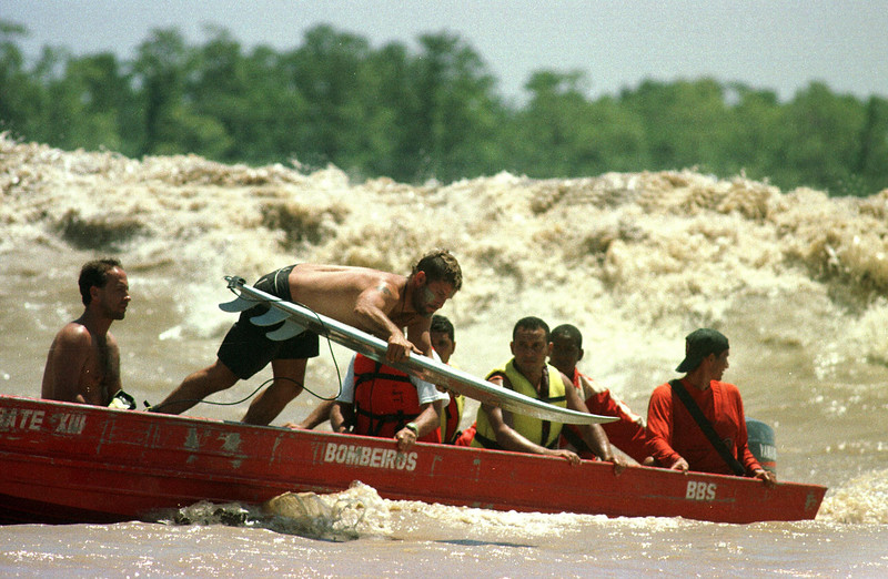 "Surfer Eraldo Gueiros jumps from a motorboat into the Araguari River as the tidal bore wave approaches during the ""I Pororoca Surf Challenge"" in Brazil's Amazonian state of Amapa. Six reknown Brazilian surfers battled the wave in two elimination heats and one final to see who could surf the wave the longest. The Araguari pororoca is possibly the most feared of all the Amazonian tidal bores, and local residents of the remote areas surrounding the mouth of the river always feared the thunderous waves which capsizes boats and washes away anything in its path twice daily. Thanks to a group of daring surfers, they have begun to see the wave in a different way: as a tourist attraction to generate money in one of the poorest regions of Brazil.(Photo/Douglas Engle)(AustralFoto/Douglas Engle)"